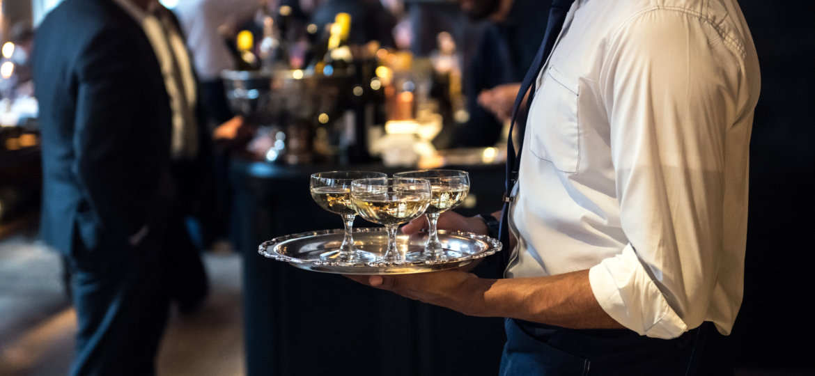Waiter from catering service carrying champagne wine drinks on t