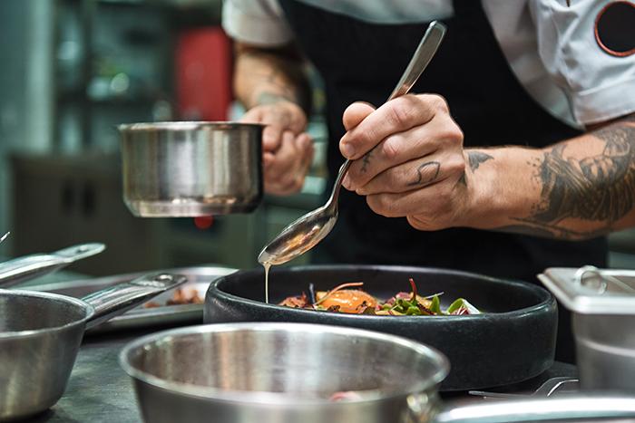 Secret recipe. Close up photo of chef hands with several tattoos adding a sauce to italian pasta Carbonara.